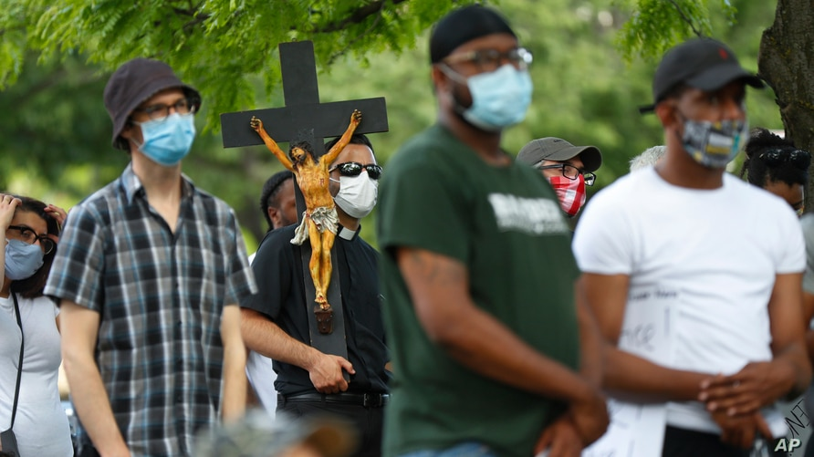 A priest carries a crucifix during a protest rally in Detroit, Thursday, June 4, 2020, over the death of George Floyd, who died…