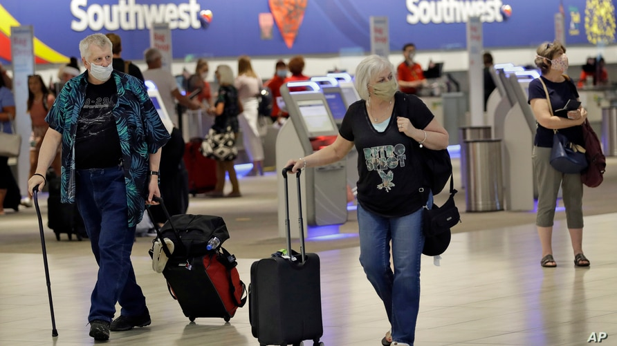 Passengers wearing personal protective face masks walk past the Southwest Airlines ticket counter Tuesday, June 16, 2020, at…