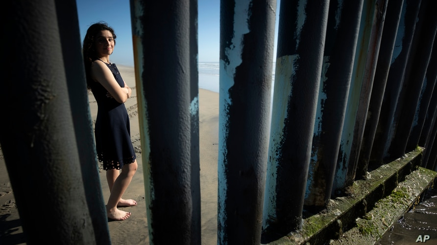 Liz Prado poses for a picture in Tijuana, Mexico, on April 23, 2020, seen through the border structure separating the two…