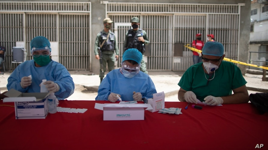 Health workers do quick tests for the new coronavirus at the Coche food market in Caracas, Venezuela, Tuesday, June 23, 2020. …