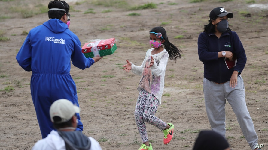 A member of the municipality hands a present to a girl from Yaruqui near Quito, Ecuador, Monday, June 1, 2020. Several private…