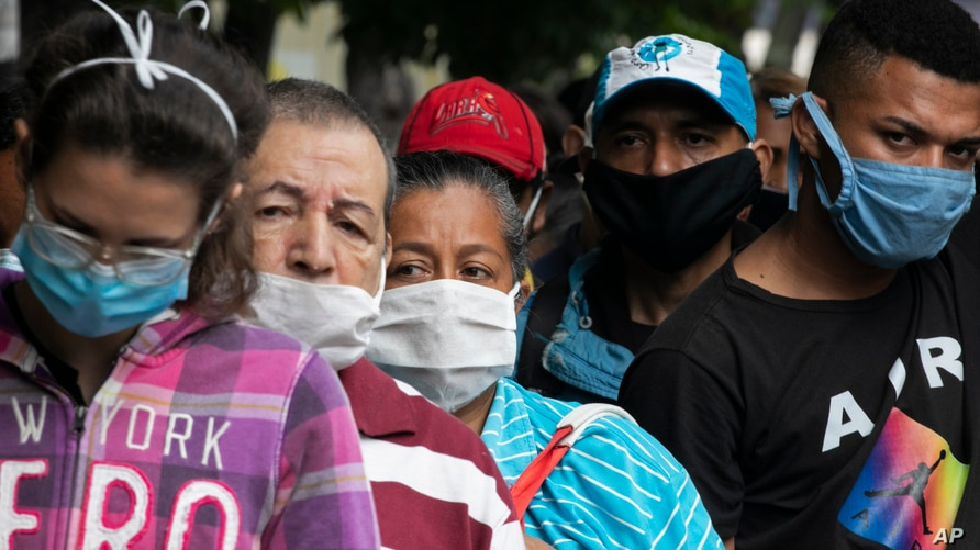 Pedestrians and commuters wearing face masks amid the new coronavirus pandemic crowd a sidewalk where buses stop in Caracas,…