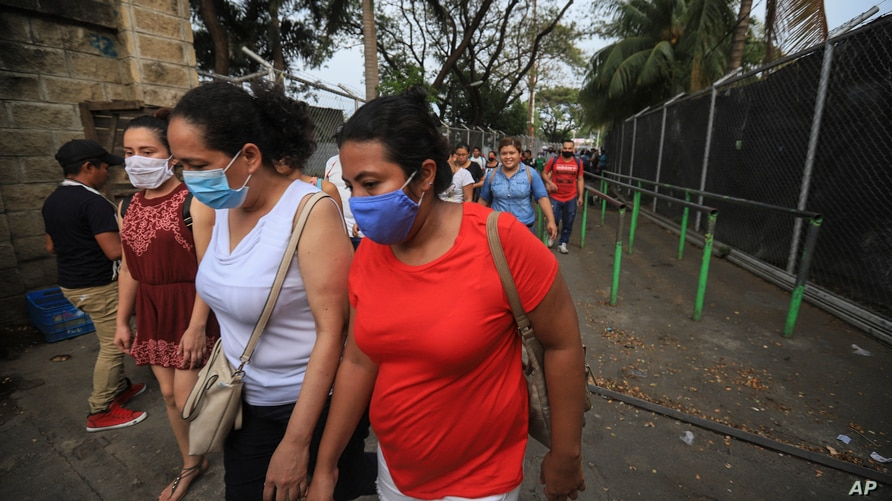 Workers wear masks as a protection against the spread of the new coronavirus as they leave from a day's work in Managua,…