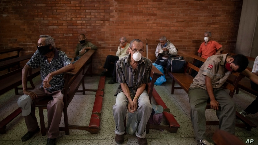 People, wearing protective face masks as a precaution against the spread of the new coronavirus, wait to receive a free meal at…
