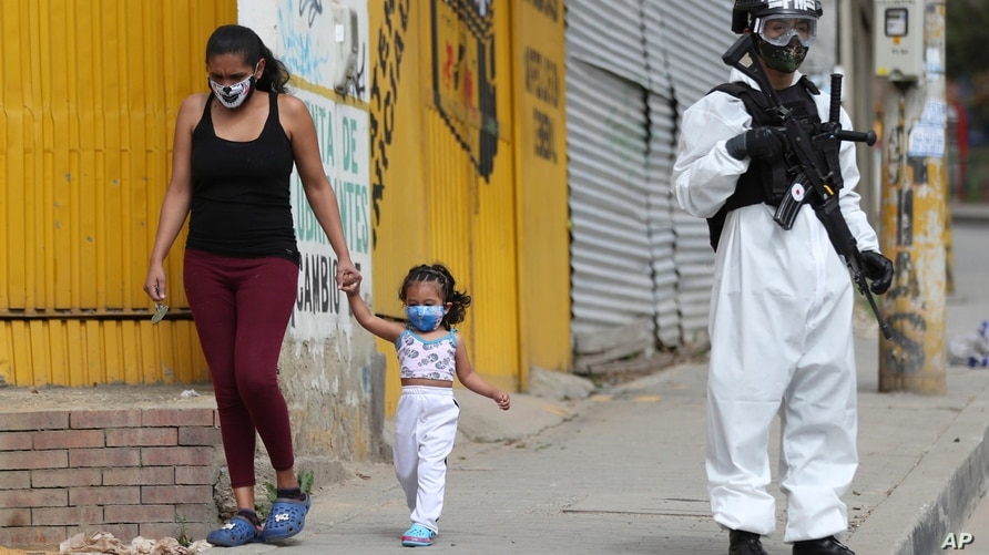 A soldier in protective gear amid the COVID-19 pandemic stands guard in Ciudad Bolivar, an area with high cases of coronavirus…