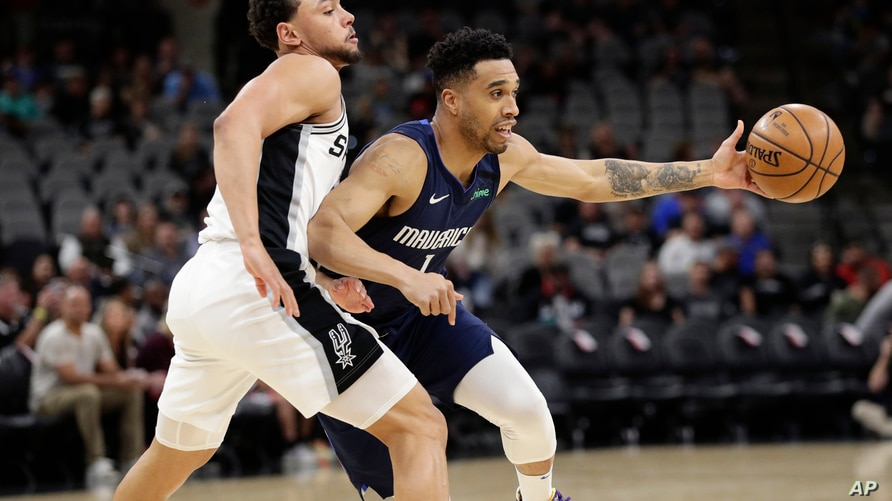 FILE - In this March 10, 2020, file photo, Dallas Mavericks guard Courtney Lee (1) drives around San Antonio Spurs guard Bryn…