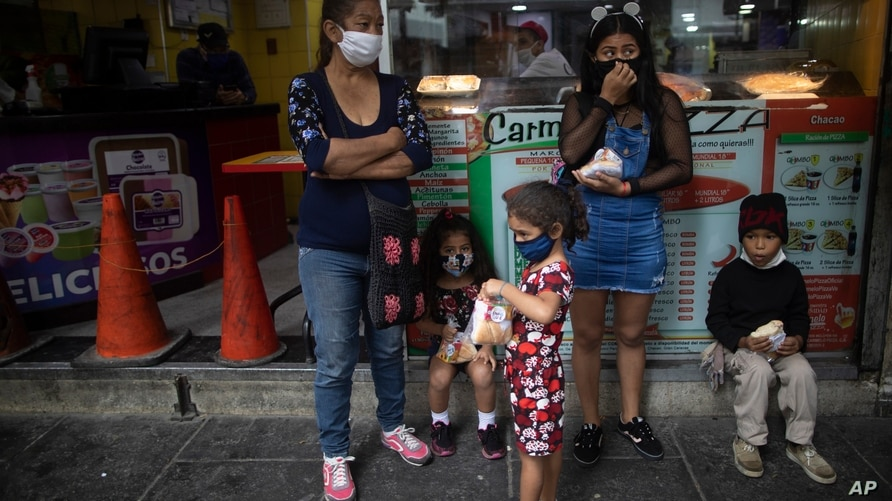 Residents, wearing protective face masks as a precaution against the spread of the new coronavirus, take shelter from the rain…