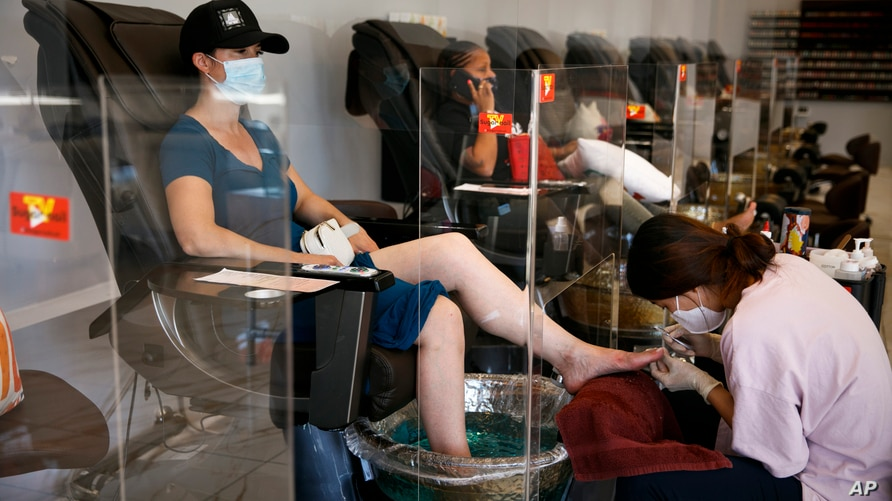 A woman with a face mask gets a pedicure at a nail shop as plexiglass dividers are installed to protect customers and employees…