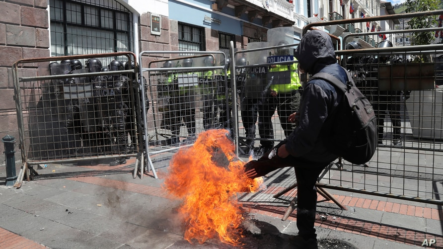 A protester kicks a burning tire at a police barricade blocking protesters from getting closer to the government palace during…