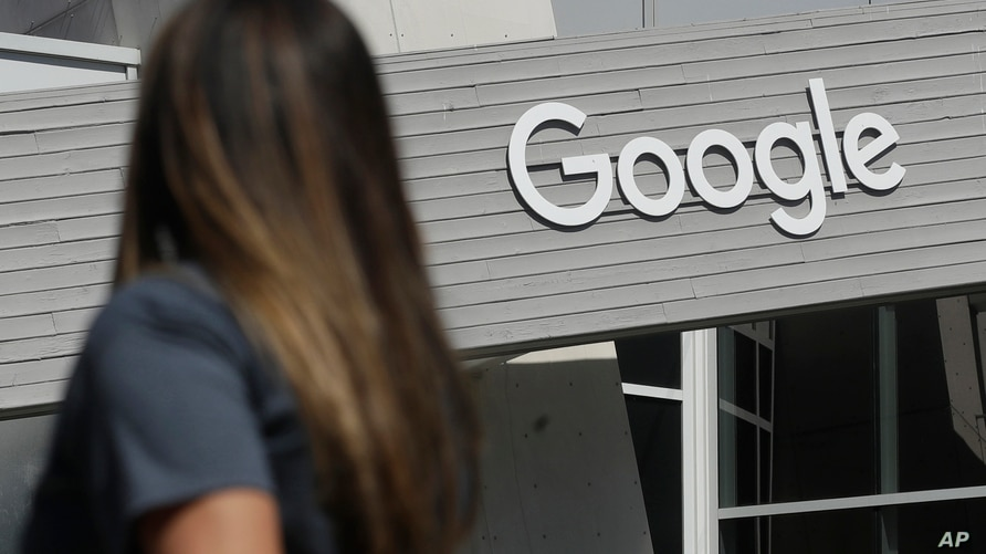 FILE - In this Sept. 24, 2019, file photo, a woman walks below a Google sign on the campus in Mountain View, Calif. New Mexico…