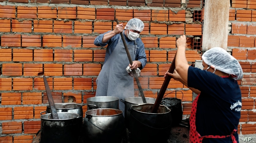 Walter Ferreira, left, and Laura Dure cook stew at a soup kitchen that feeds about 300 people daily in Luque, Paraguay, Monday,…