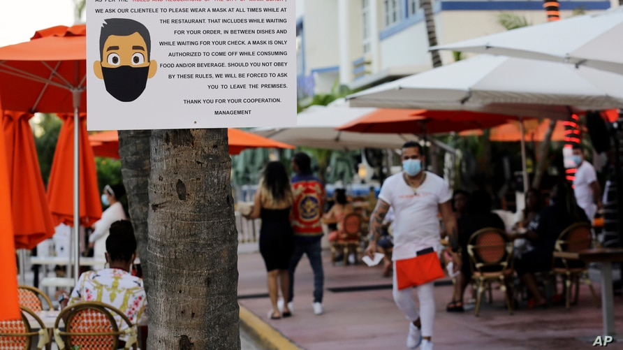 A sign informs customers at the Edison Hotel restaurant about wearing a protective face mask during the coronavirus pandemic,…