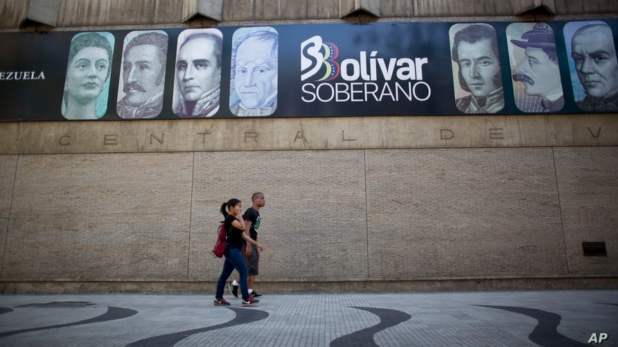 FILE - In this Aug. 20, 2018 file photo, pedestrians walk past the Central Bank displaying a banner featuring the faces that…