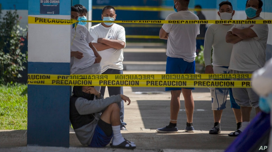 Deportees stand in an Immigration Institute shelter where Guatemalans deported from the U.S. are being held in quarantine,…