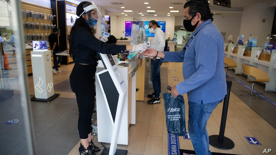 A mobile phone store employee wearing a mask and face shield to curb the spread of the new coronavirus tends to a client at a…