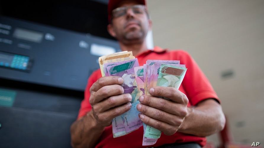 In this Oct. 8, 2019 photo, gas attendant Orlando Godoy counts his Bolivars bills in San Antonio de los Altos on the outskirts…
