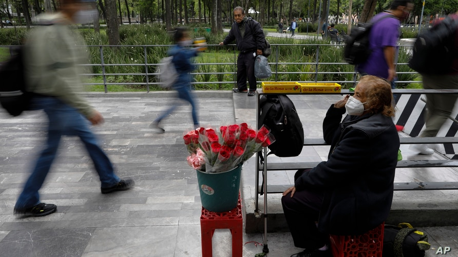 Wearing a mask to help prevent the spread of the new coronavirus, Martha Gonzalez Reyes, 76, sells roses outside Metro Hidalgo…
