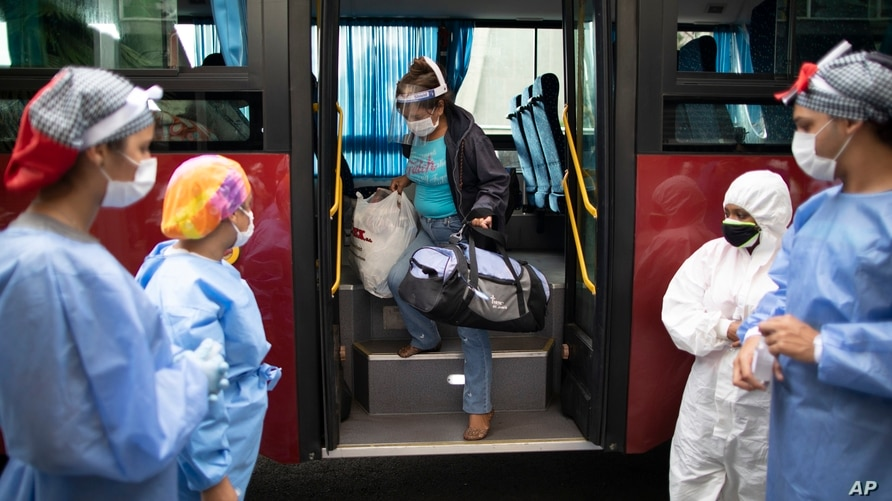 A woman who tested positive for COVID-19 arrives on a government bus to a former students residence being used to quarantine…