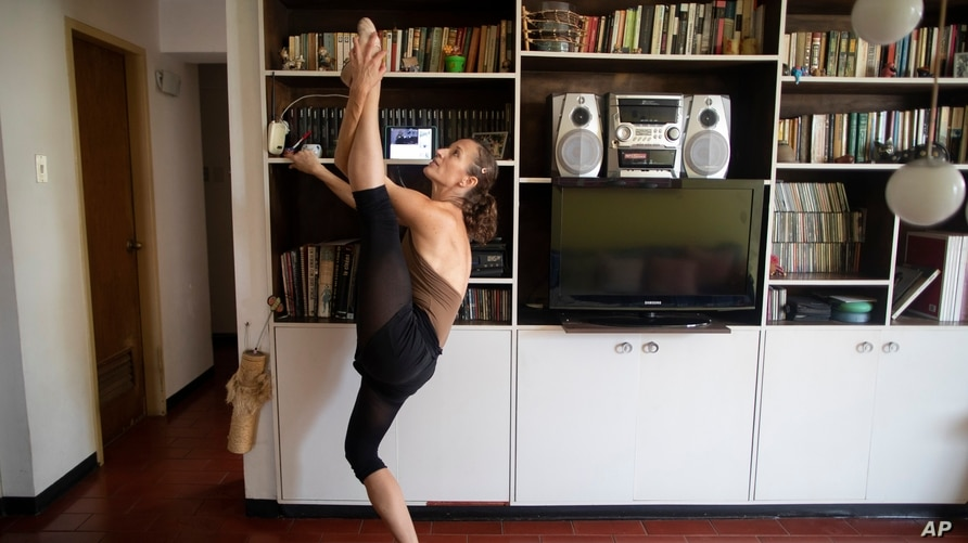 Carolina Wolf, who dances with Venezuela's national ballet, trains in her living room as she follows a youtube video by Ernst…