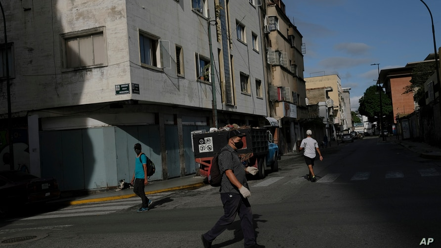 Pedestrians wearing protective face masks as a precaution against the spread of COVID-19, walk in the Chacao neighborhood of…