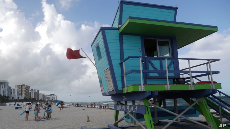 A red flag flies from a lifeguard station indicating high surf, Friday, July 31, 2020, in Miami Beach, Fla. Forecasters…