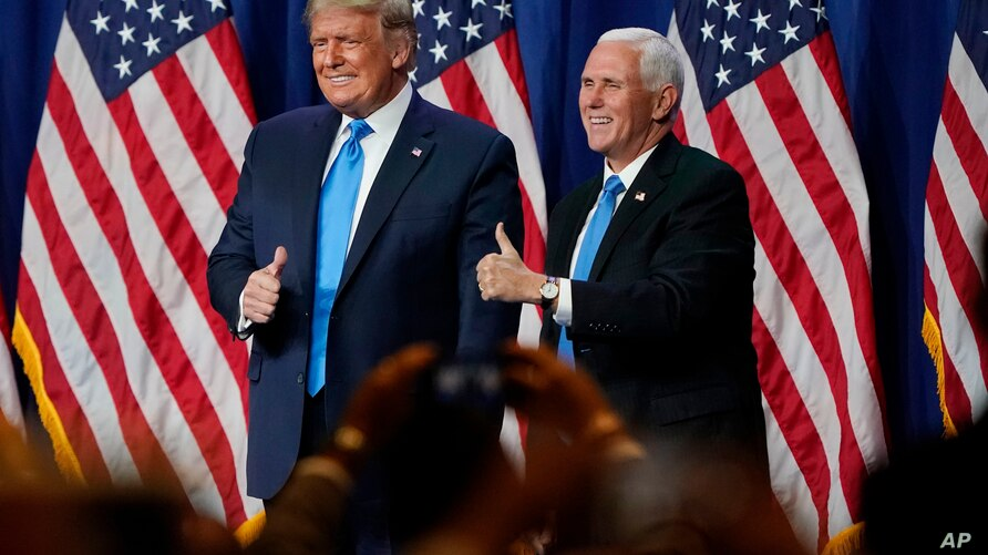 President Donald Trump and Vice President Mike Pence give a thumbs up after speaking during the first day of the Republican…