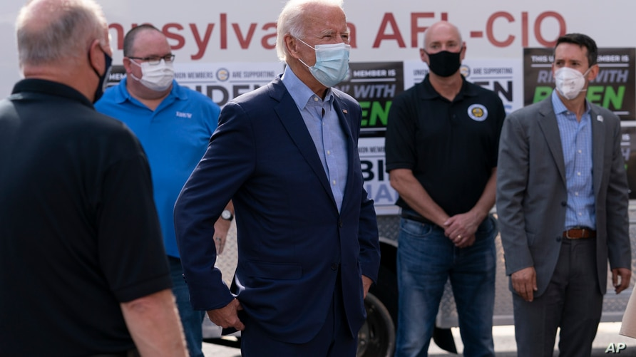 Democratic presidential candidate former Vice President Joe Biden talks with union leaders after taking photographs outside the…