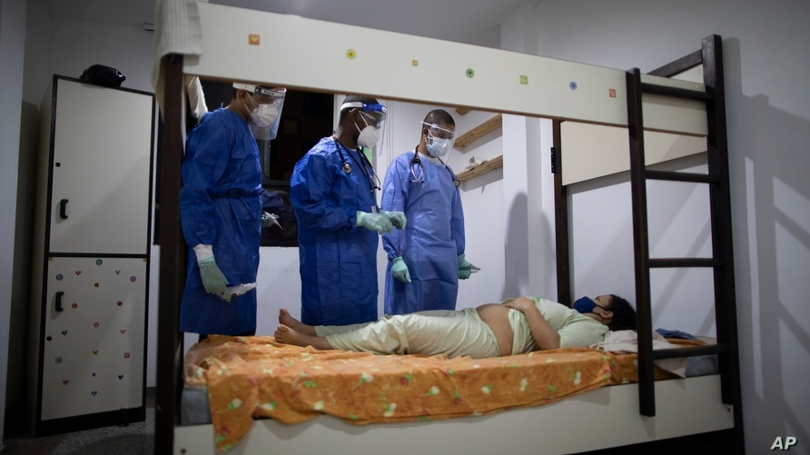 Venezuelan doctors check on an COVID-19 patient lying in bed complaining of pain in her belly, in her room at former students…