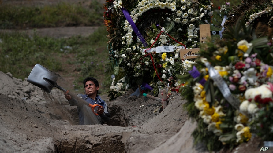 A cemetery worker digs a grave in a section of the Valle de Chalco Municipal Cemetery which opened early in the coronavirus…