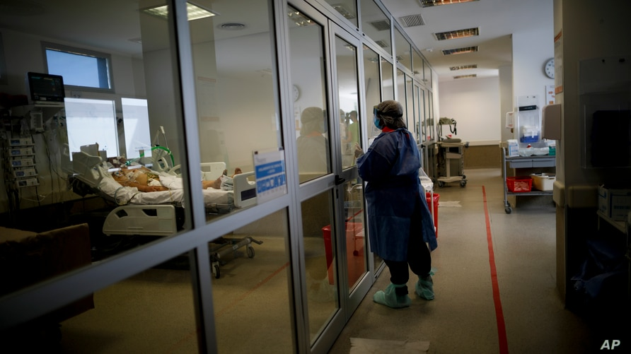 A woman watches a relative at the COVID-19 intensive care unit of a hospital in Buenos Aires, Argentina, Tuesday, Sept. 15,…
