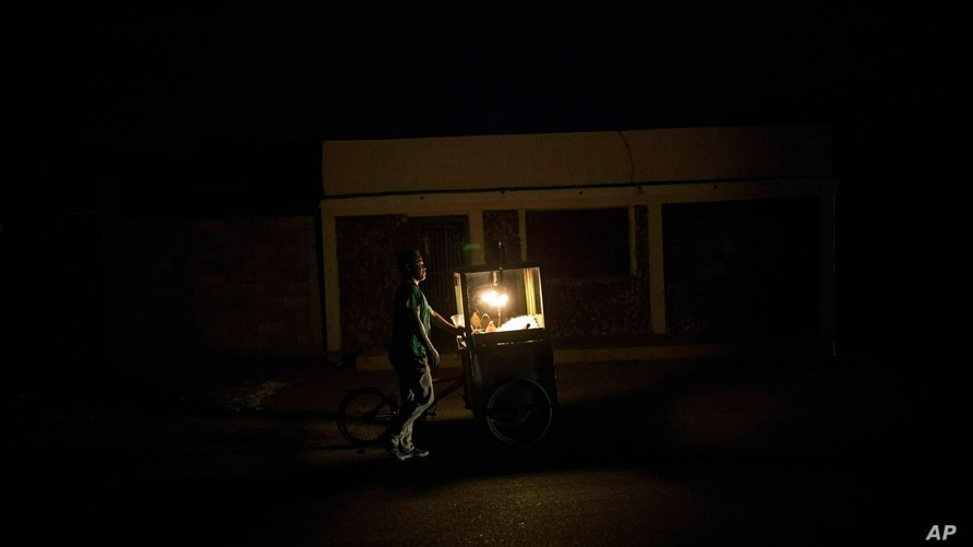 In this May 15, 2019 photo, popcorn vendor Raul Navas looks for customers during a black out in Maracaibo, Venezuela. Navas…