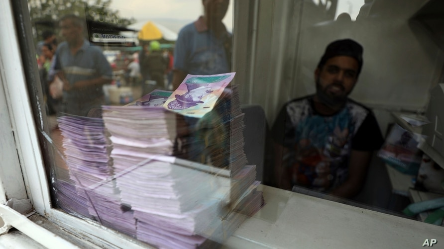 Bills of Venezuelan currency can be seen stacked at a currency exchange booth in La Parada, on the outskirts of Cucuta,…