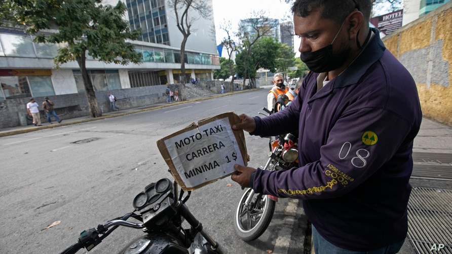 """A moto-taxi driver, wearing a face mask amid the new coronavirus pandemic, places a price sign that reads in Spanish """"Minimum 1…"""