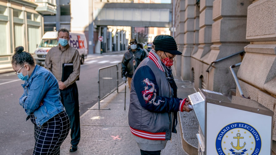 Joy Little drops off a mail ballot into an official ballot drop box as voters wait in line at City Hall as in-person early…