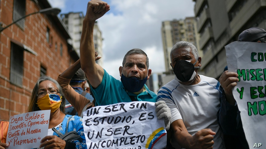"""A man shouts slogans as he holds the Spanish quote: """"An uneducated person is an incomplete person. Bolivar."""" at a demonstration…"""