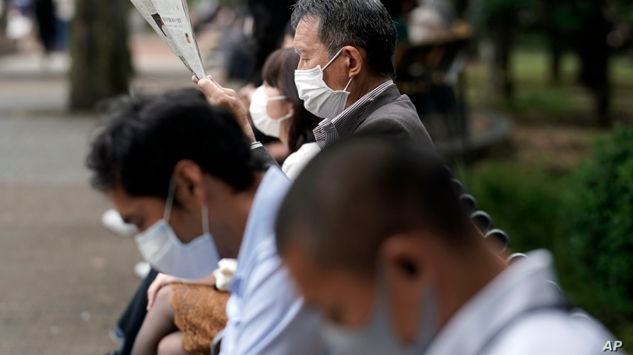 People wearing protective masks to help curb the spread of the coronavirus rest at a park Wednesday, Oct. 14, 2020, in Tokyo…