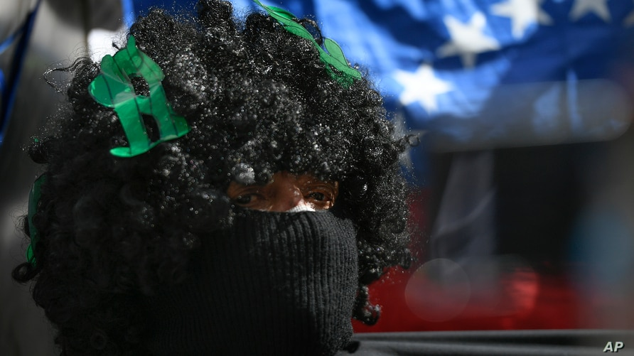 A protester wearing a wig covered with US dollar signs shouts slogans during a demonstration by teachers demanding better…