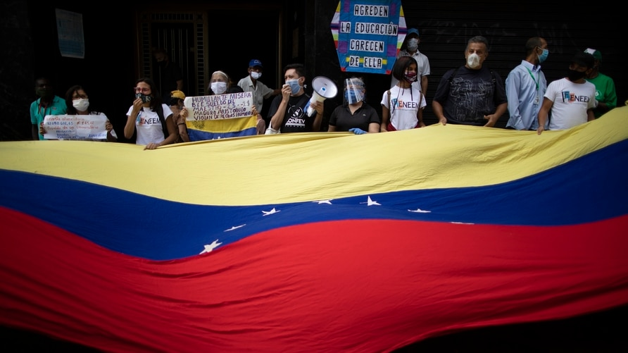 Protesters wave a Venezuelan flag during a demonstration by teachers, who make $2 dollars a month, to demand higher salaries in…