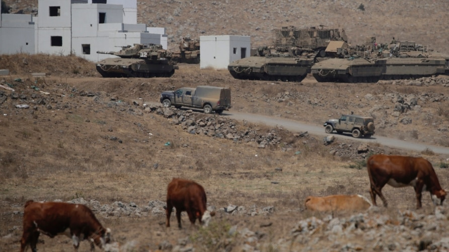 Israeli military tanks and vehicles maneuver during an exercise in The Israeli controlled Golan Heights near the border with…