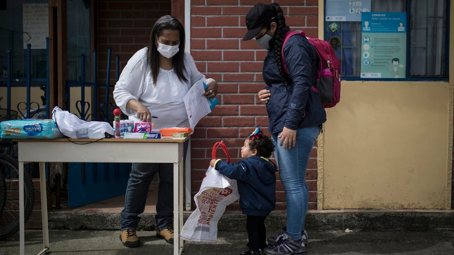 Colombian resident Alba Rada gifts toiletries and food to Venezuelan migrant Rosmira Camacho and her child, outside Rada's home…