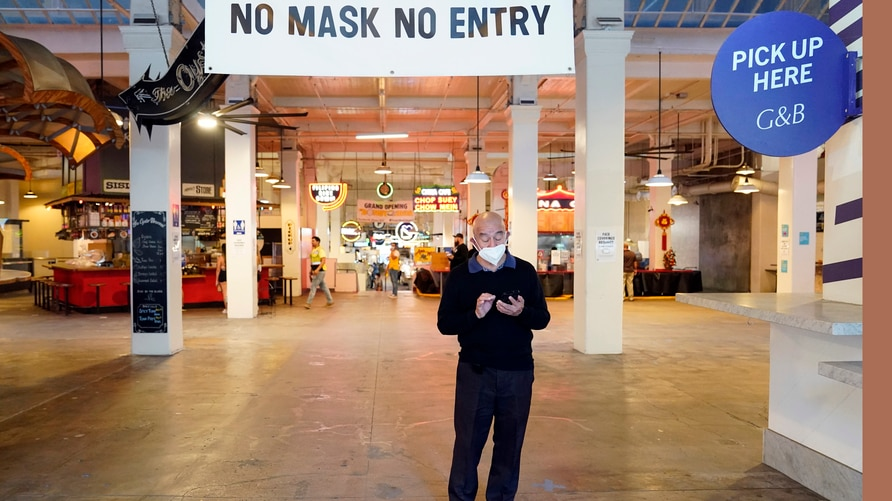 FILE - In this Nov. 16, 2020, file photo, a sign points to a mask mandate at the Grand Central Market in Los Angeles. Gov…