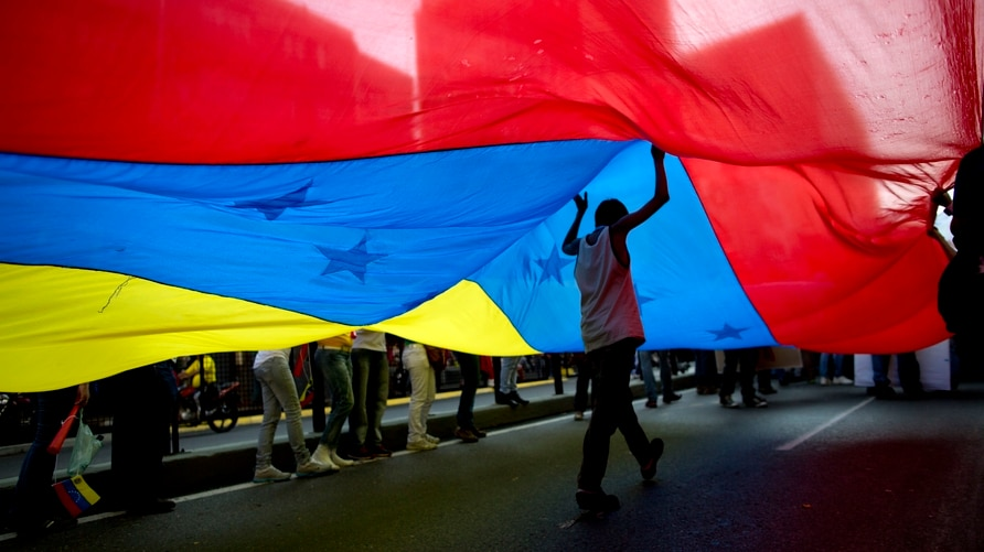 A youth walks under a large Venezuelan flag during a rally organized by workers of the National Telecommunications Company or…
