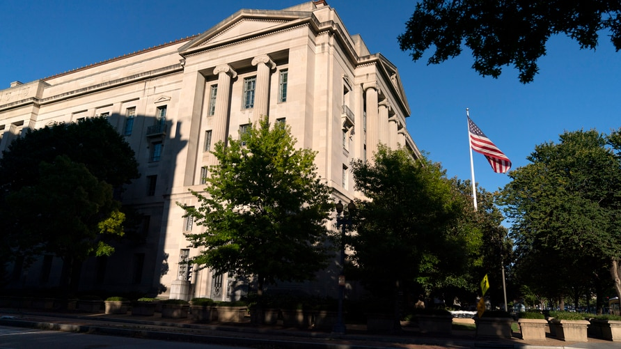 The American flag flies outside of the Justice Department building, Thursday, Oct. 8, 2020, in Washington. (AP Photo/Jacquelyn…