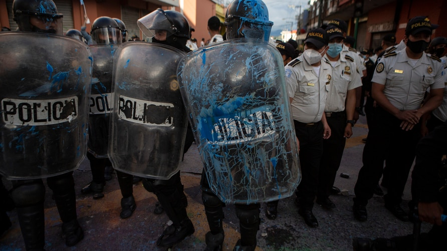 A riot police gets covered in blue paint by demonstrators near the Congress building after protesters set a part of the…