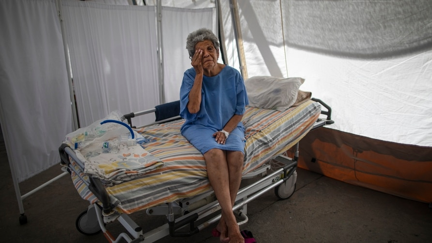 Nancy Rodriguez, a 76-year-old COVID-19 patient, wipes tears as she explains her battle with the virus under a tent for…