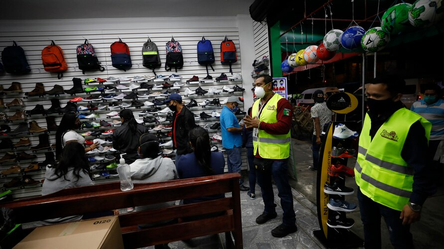 Municipal public safety officers inform workers and customers in a shoe store that businesses should be closing for the day in…