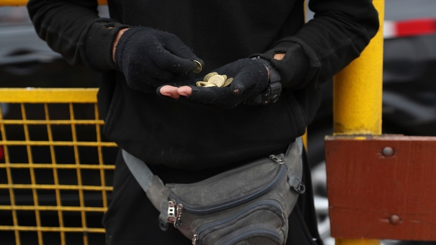 In this Oct. 8, 201 photo, Venezuela's migrant Freddy Brito counts coins he earned singing for tips in a public bus in Lima,…