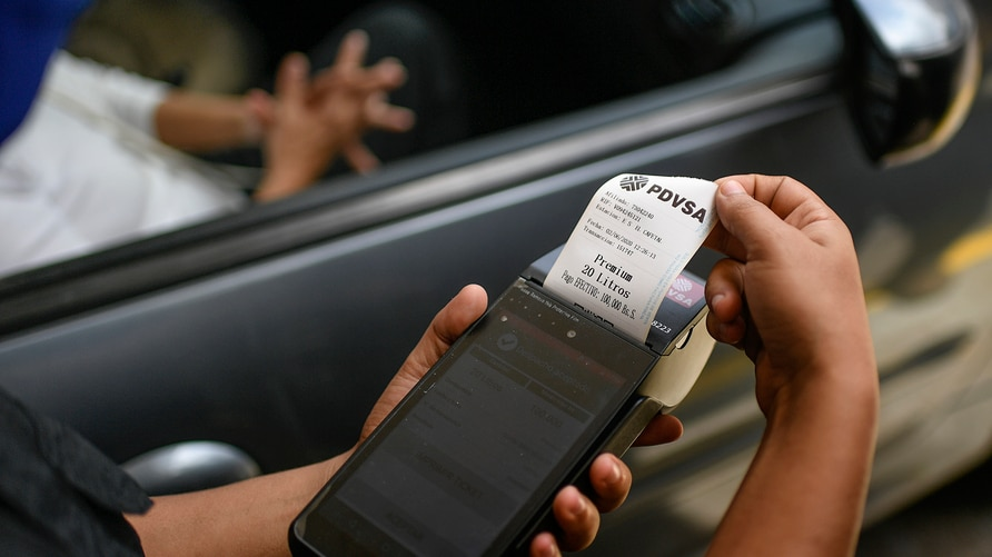 A biometric machine prints out a voucher at a state oil company gas station in Caracas, Venezuela, Tuesday, June 2, 2020…