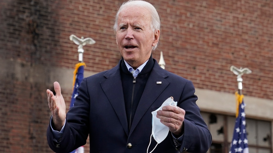 President-elect Joe Biden walks onstage to speak at a drive-in rally for Georgia Democratic candidates for U.S. Senate Raphael…