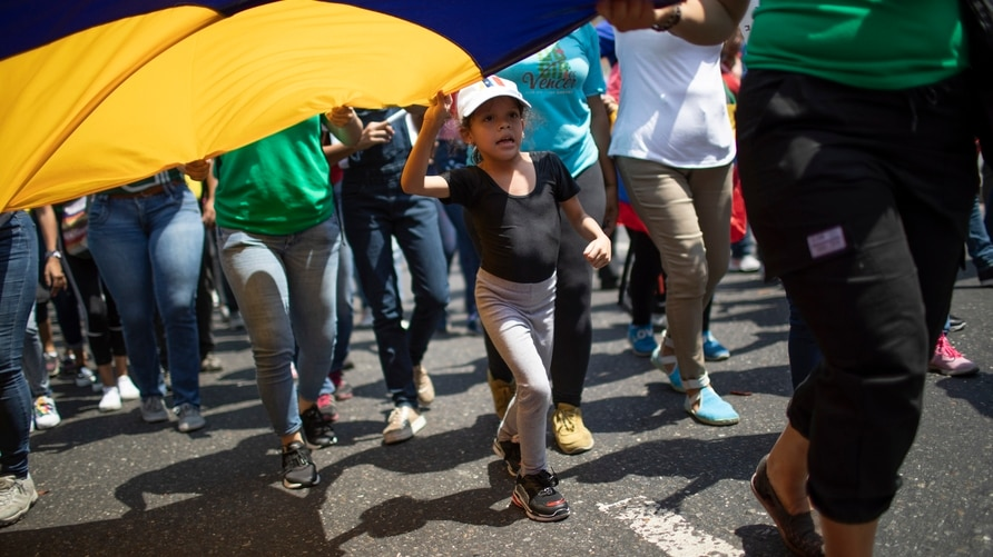 A little girl marches as she helps to hold a Venezuelan national flag at a pro-government march on International Women's Day in…